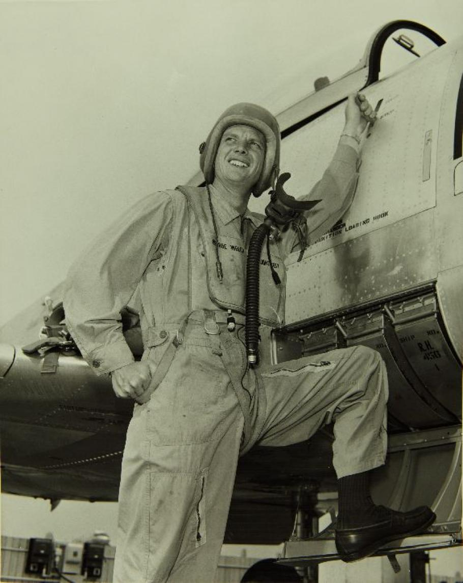 Man in flight suit standing on aircraft