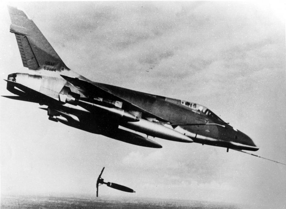 "A black and white photo of a North American F-100D aircraft in flight dropping a ""Snake eye"" bomb on a suspected Viet Cong position in 1966."