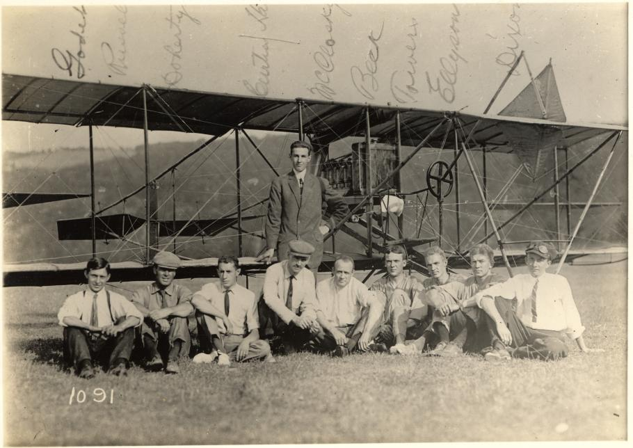 Eight men sitting, one man standing in front of airplane
