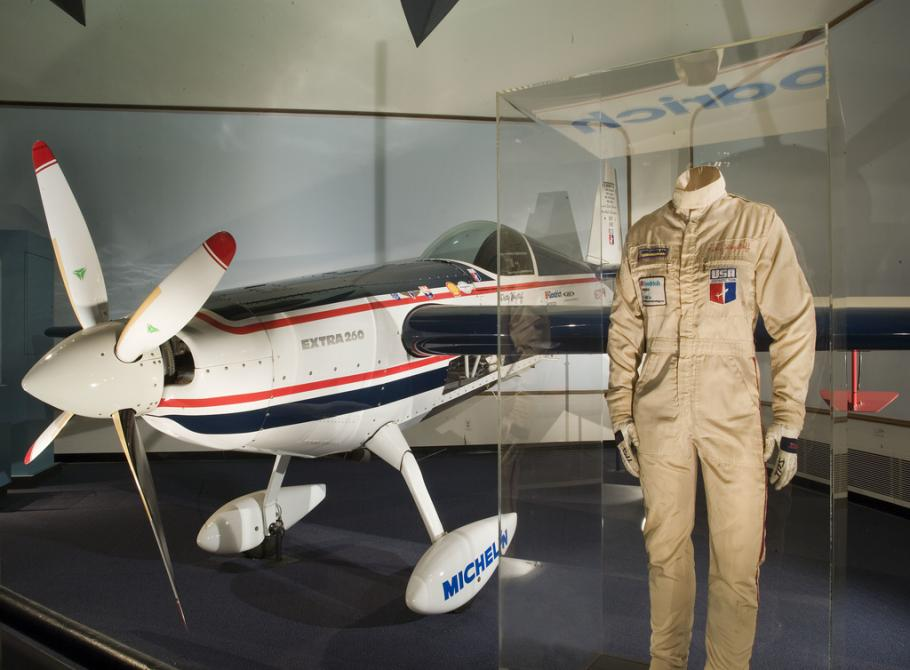 White airplane on display with flight suit next to it