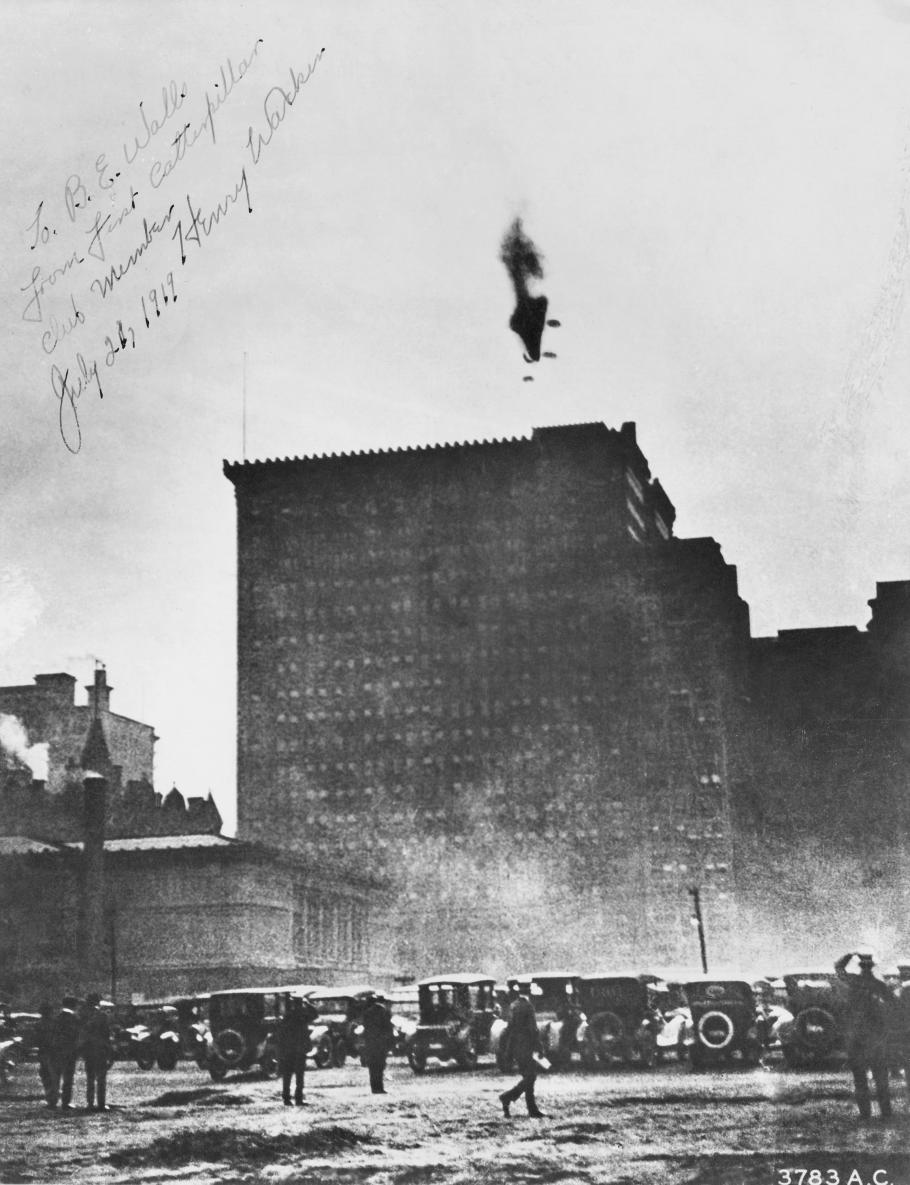 Cars below a building with a crashing airship