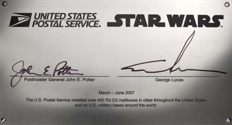 The R2-D2 collection box signature plate, signed by George Lucas and Postmaster General John E. Potter.