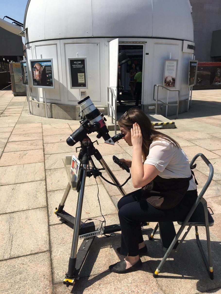 Volunteer Anne Ahrendsen using a telescope outside of the Phoebe Waterman Haas Public Observatory.