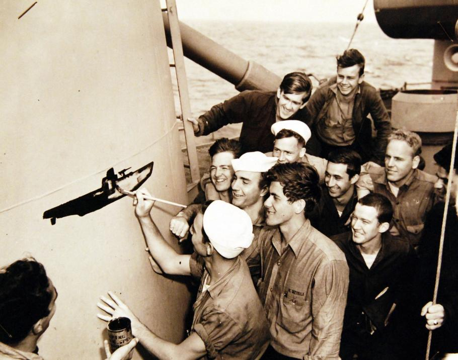 Crewmen draw submarine on side of ship