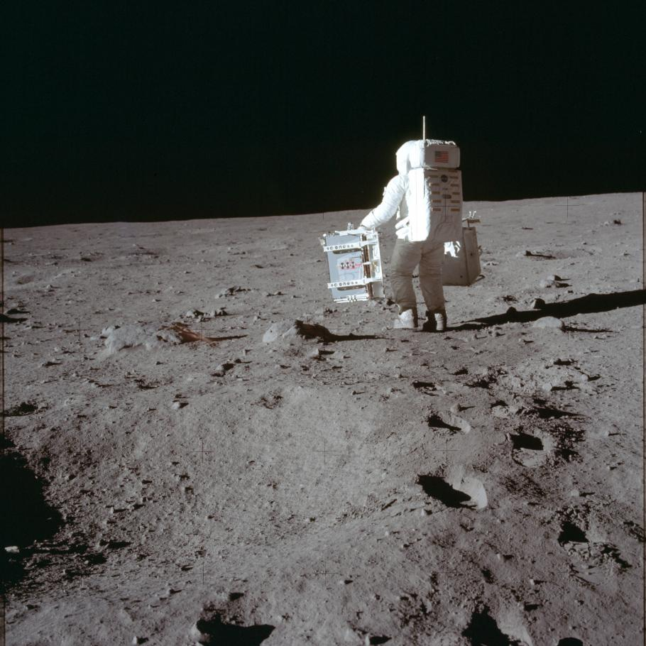 Aldrin photographed from behind on the Moon carrying equipment.