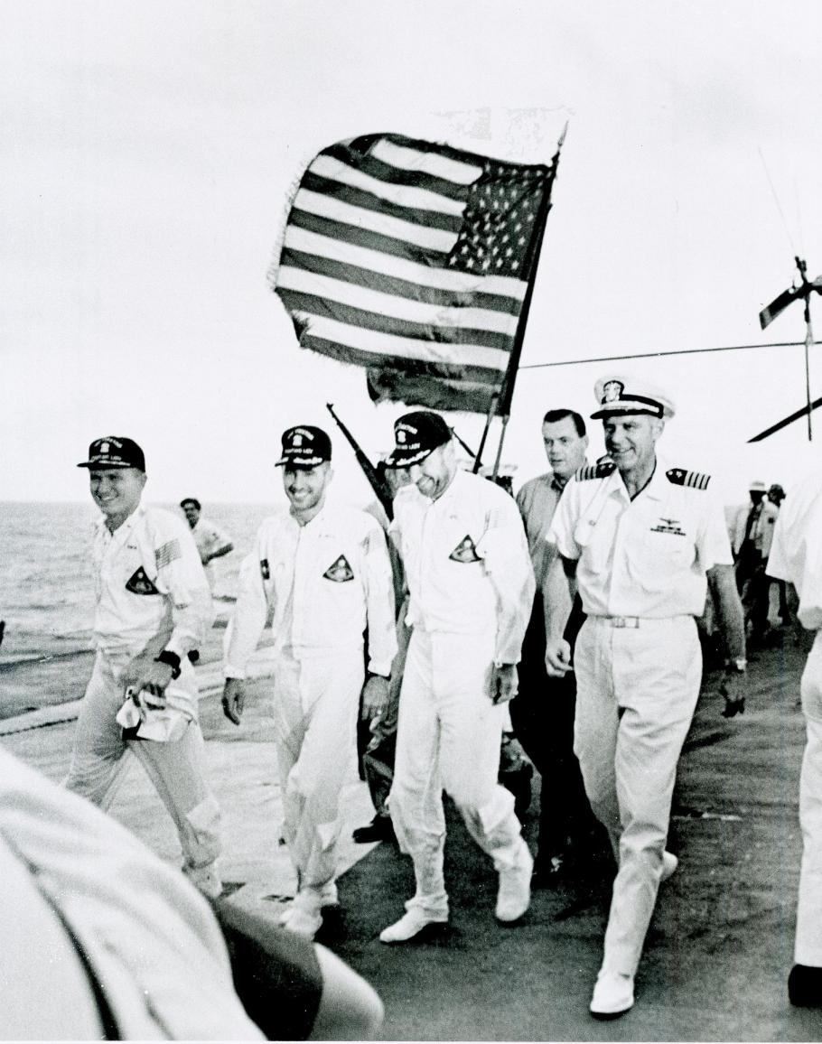 Apollo 8 astronauts and commanding officer of the recovery ship U.S.S. Yorktown walk the red carpet of the flight deck after splashdown recovery in the Pacific Ocean