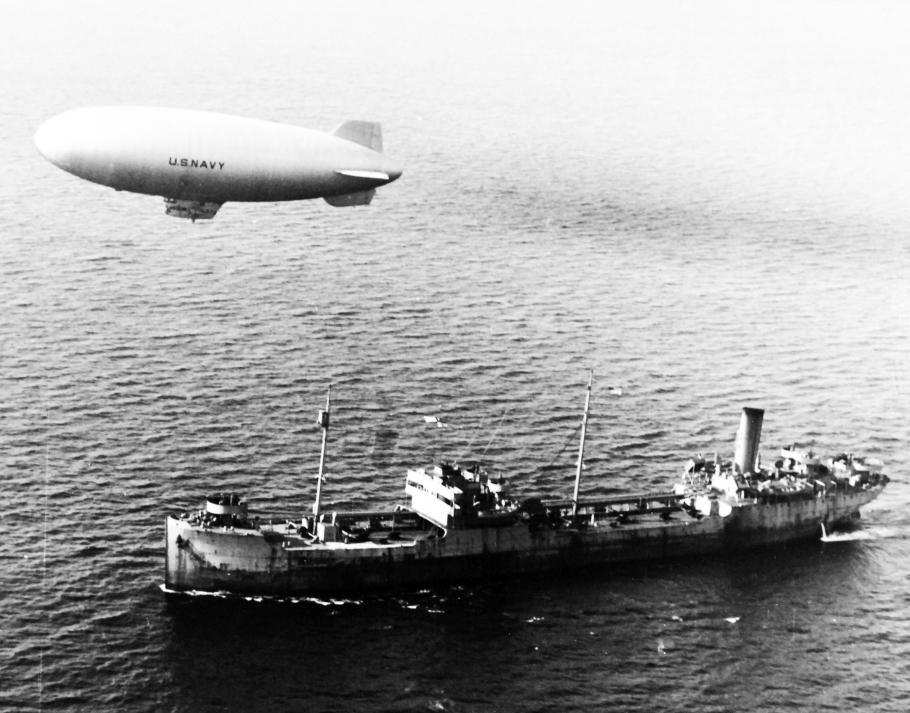 Blimp flying above merchant ship