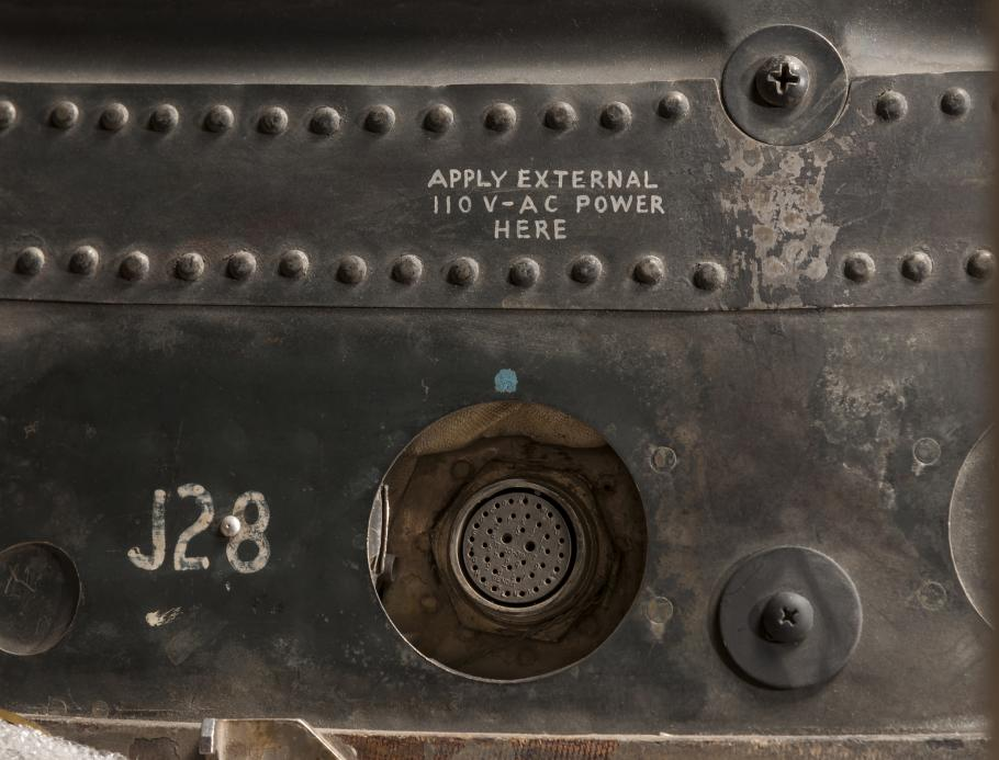A close up of the exterior of the spacecraft. A plug and notations can be seen.