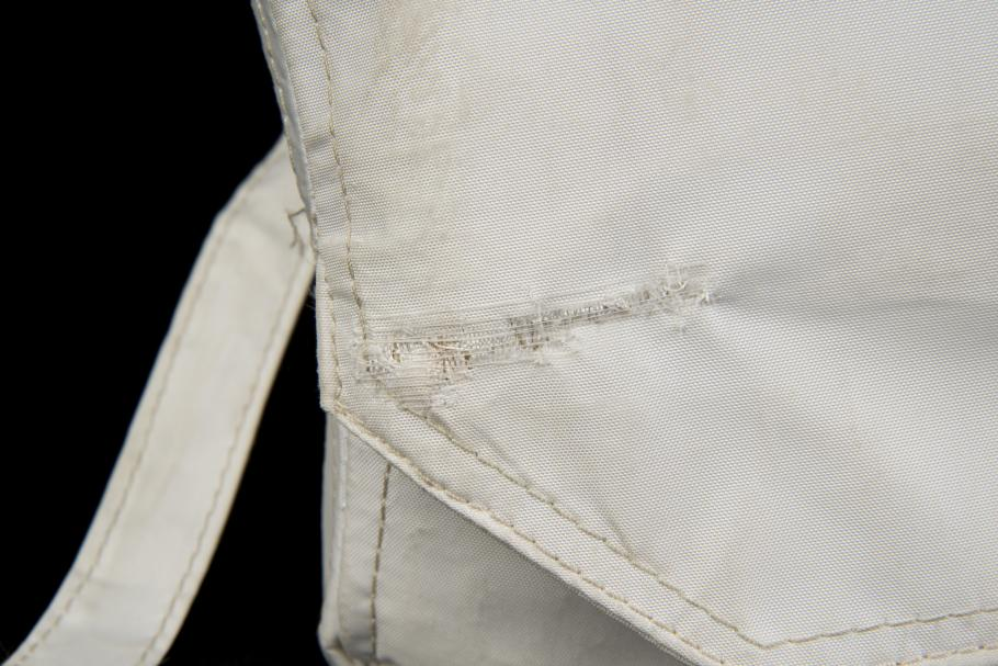 Detail view of repair made to the tear in Beta cloth medical container.
