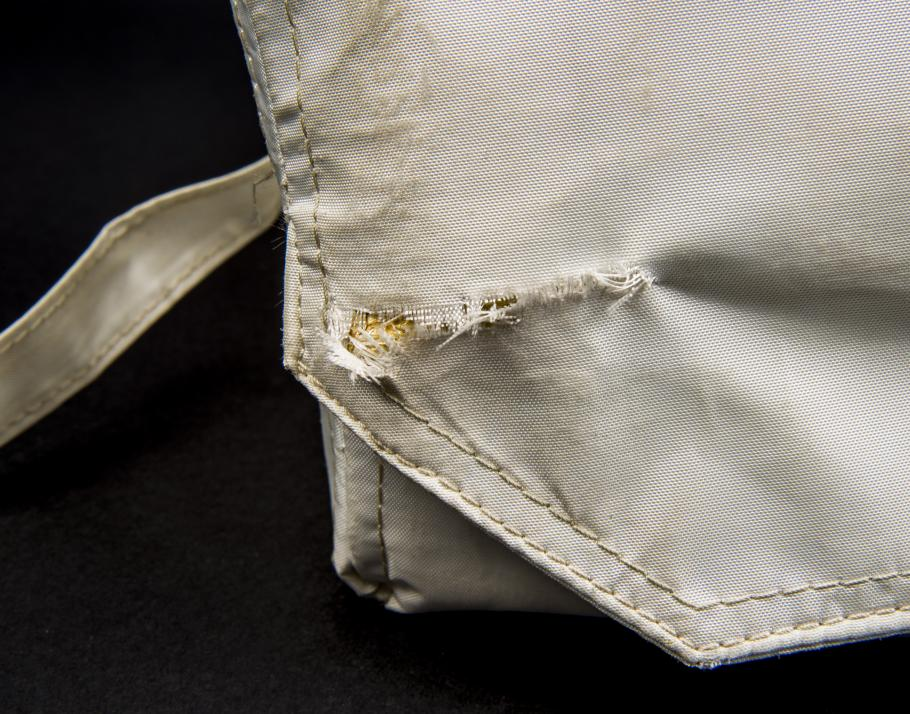 Detail view of the tear to the Beta cloth of the Apollo 11 medical accessory kit.
