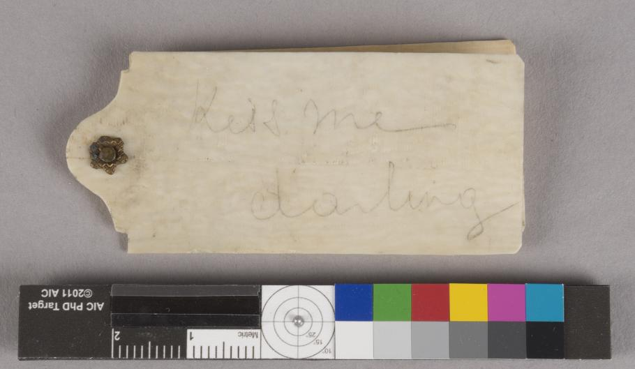 "A photograph of the ivory dance card with the inscription ""Kiss me darling."""