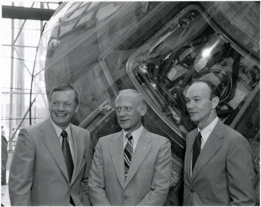 Black and white of Armstrong, Aldrin, and Collins stand beside the Apollo 11 command module.