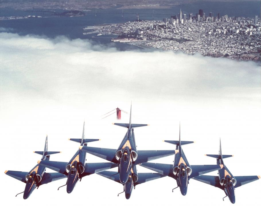 The U.S. Navy Blue Angels in formation flying over the Golden Gate Bridge