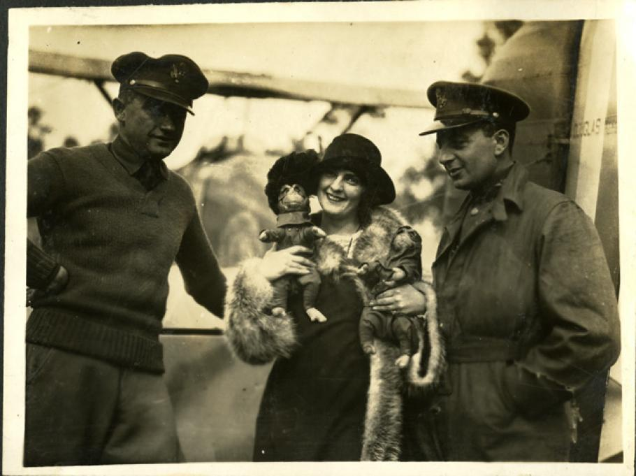 A woman holding two monkeys