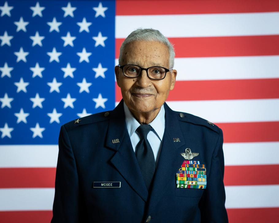 Man in military uniform in front of American flag