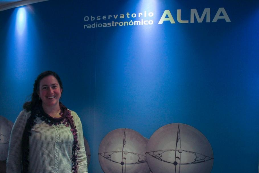 Image of Genevieve in front a sign for the ALMA observatory.
