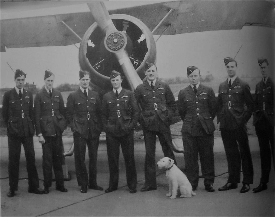Eight airmen in front of aircraft with dog