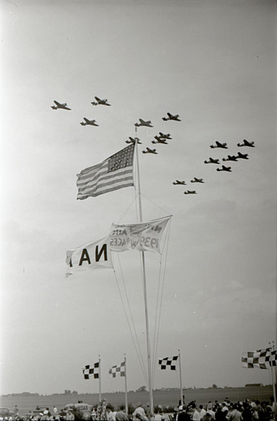 Formation of airplanes fly past American flag. Spectators can seen at bottom.
