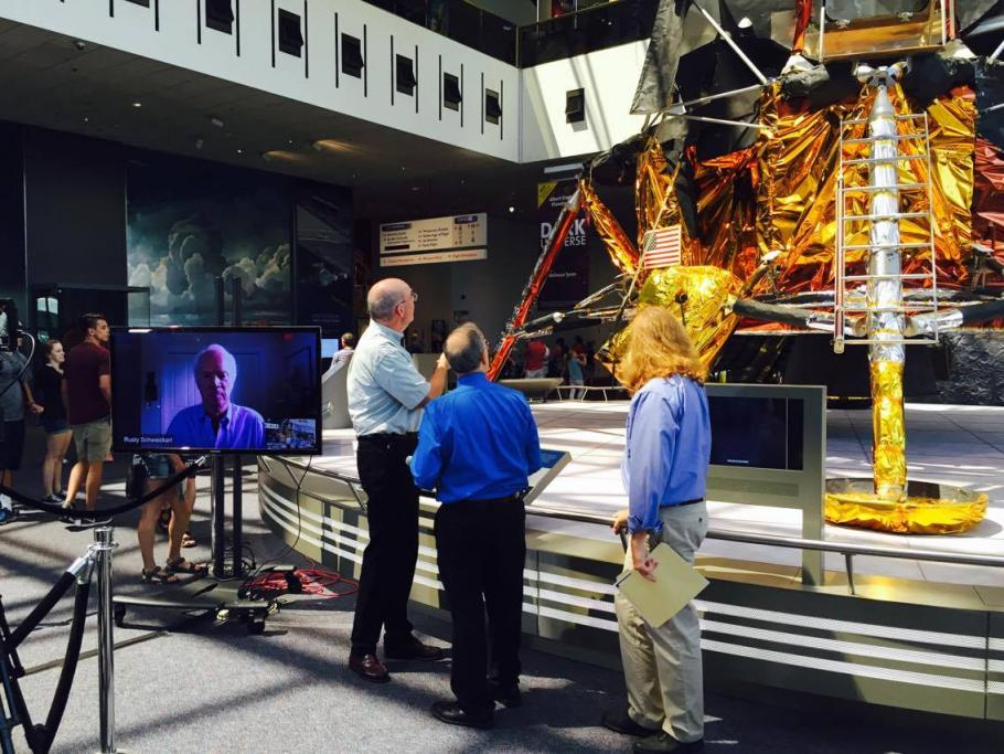 Three speakers with backs to camera look at the lunar module. Next to them is a TV screen with guest astronaut.