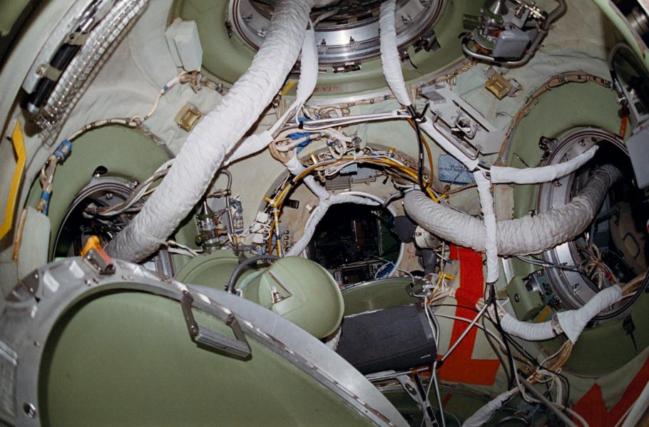 View inside the Mir space station, wires and cords are visible from one module to the next.
