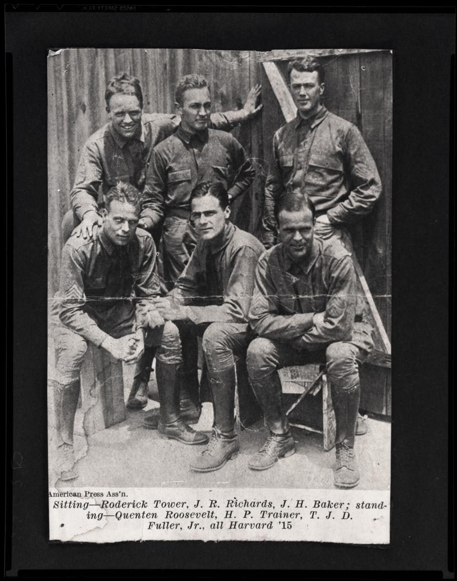 Three men stand behind three men sitting, all in uniform