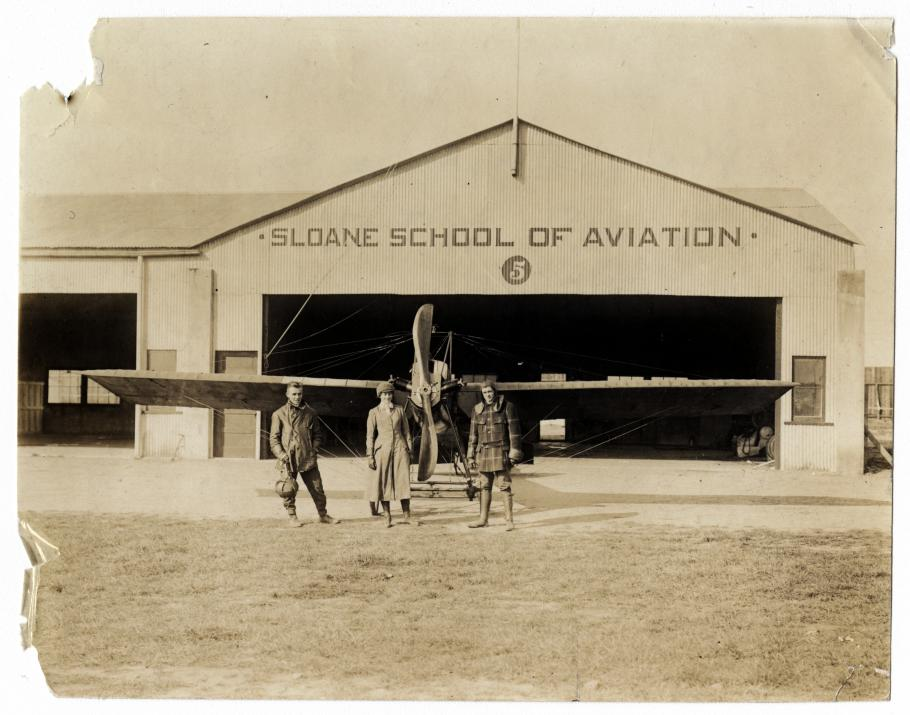 Two men and a woman in front of a hangar and airplane