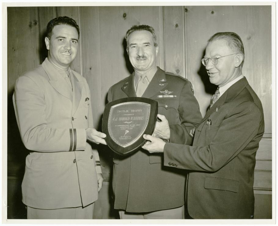 Two men present plaque to man between them