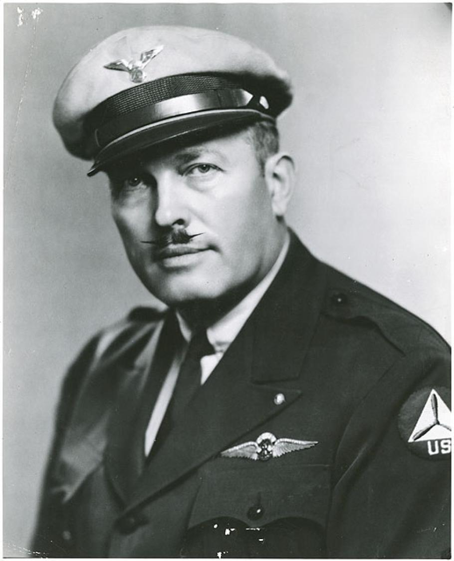 "Half length black and white photograph of man, wearing a full-brim light-colored wheel hat with winged insignia and uniform with ""RT"" insignia wings over breast pocket. He has a mustache with pointed tips."