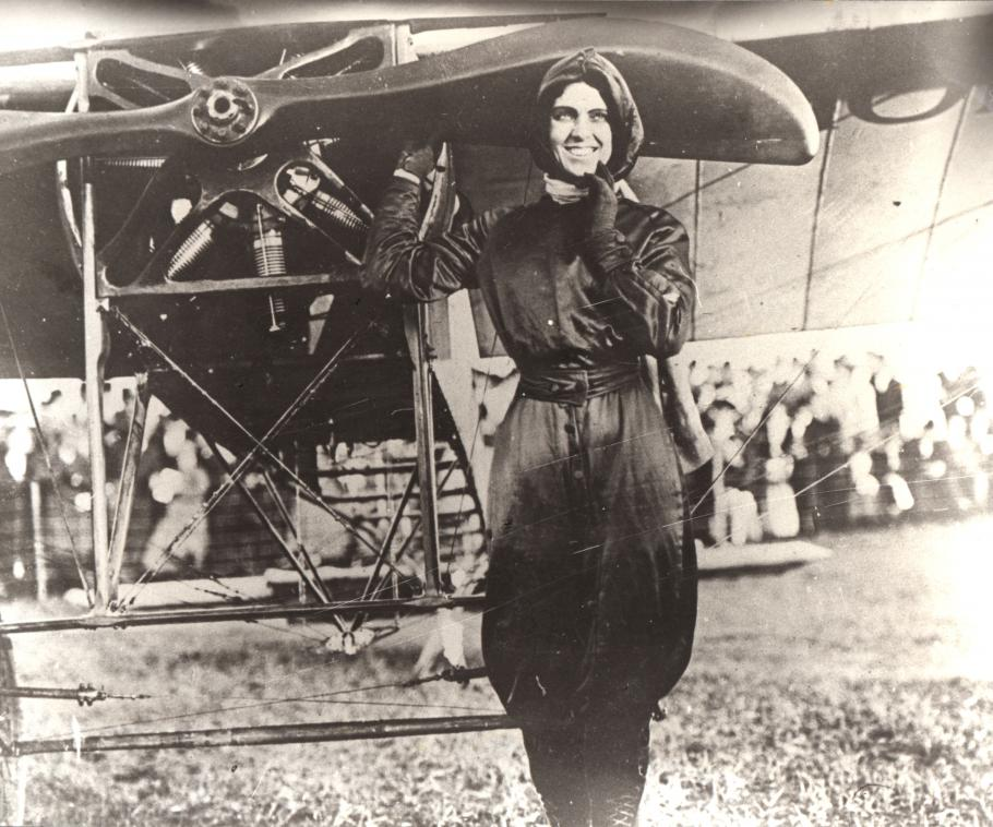 Woman in flying gear poses in front of an airplane. Right hand on propeller, left hand on her chin. Crowd in background.