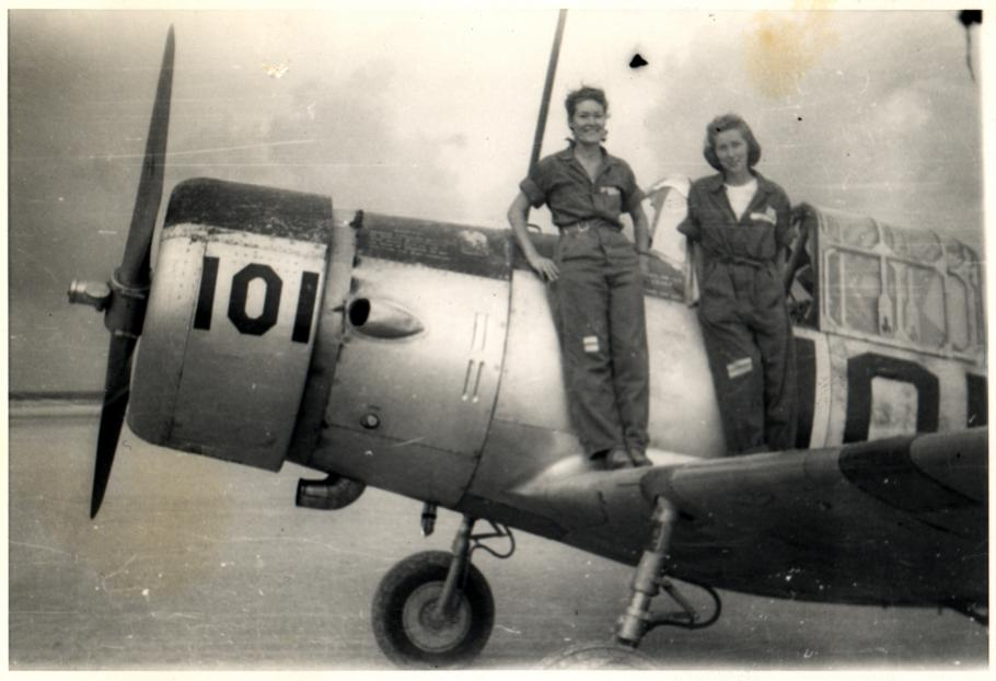 two women stand on wing of aircraft