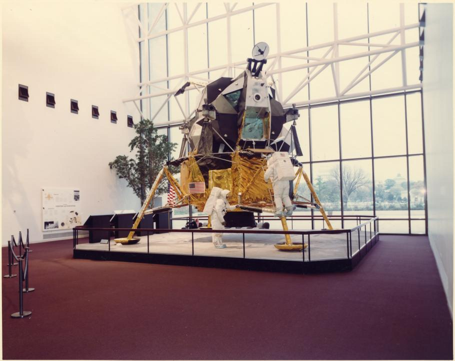 Lunar Module with protective railing on red carpet.