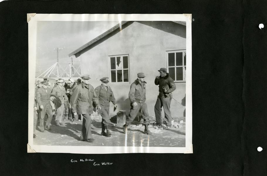Black scrapbook page. Centered photo in photo corners: 3 men in uniform (Gen. Douglas MacArthur 3rd on the left) walk in front of a building. Background left: group in uniform following. Background right: Man in leather jacket and cap.