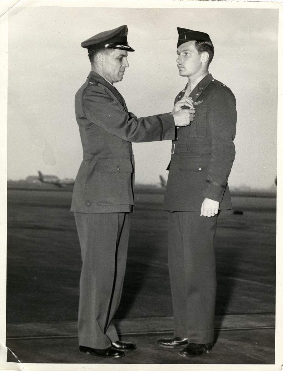 (Left) Man in military uniform and hat pins an award on man in cap on right. Air field with aircraft in background.