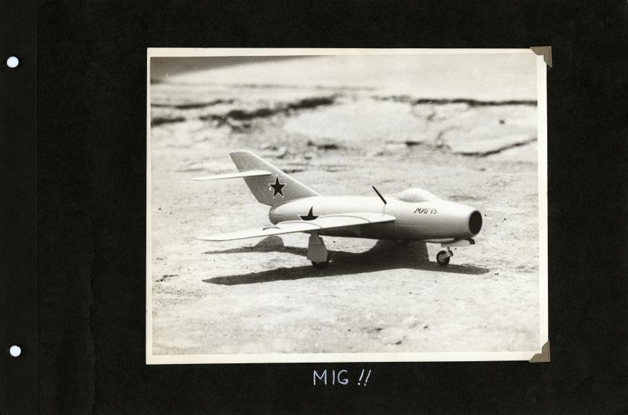 """Black scrapbook page with photo of the right side of model airplane with star on tail and fuselage centered. Handwritten white text below reads: """"MIG!"""""""