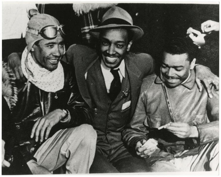 Three men pose.