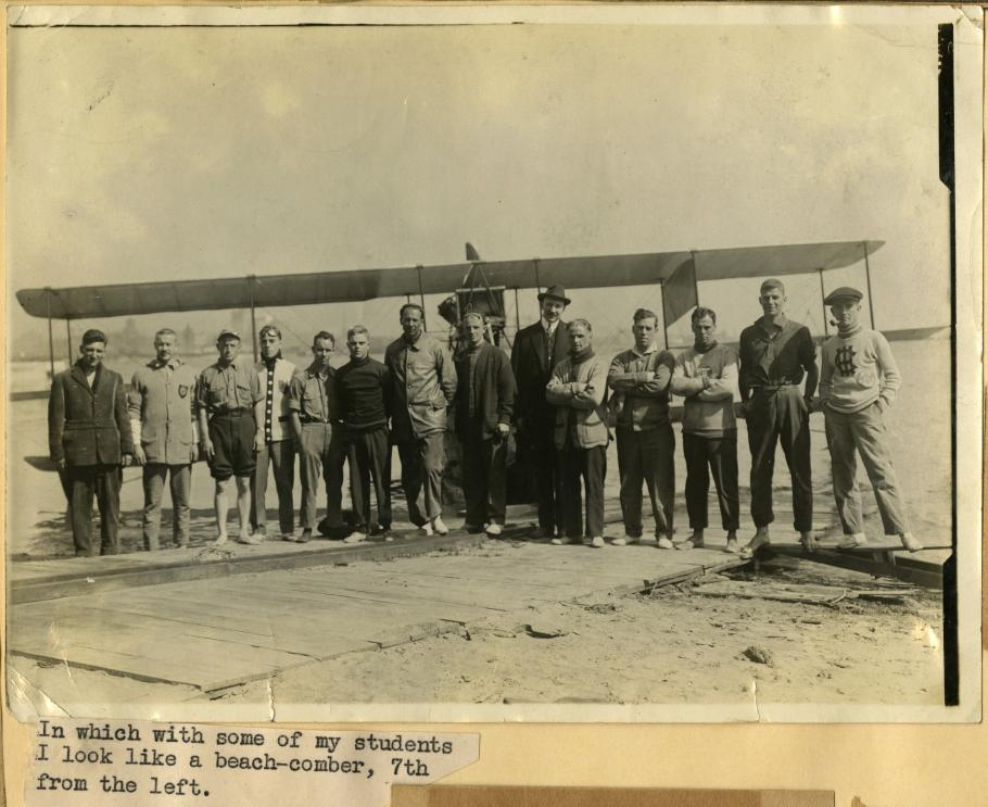 Fourteen men stand in front of an airplane