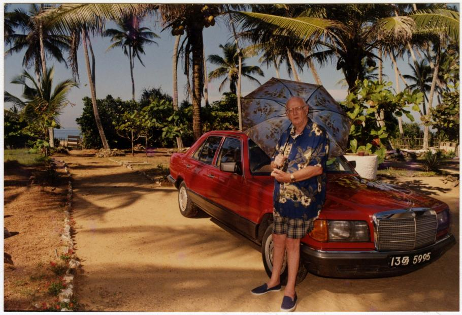 Arthur Clarke near the beach in Sri Lanka, leaning on his car, early 2000s.