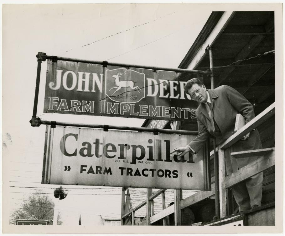 Man points to sign for caterpillar tractors