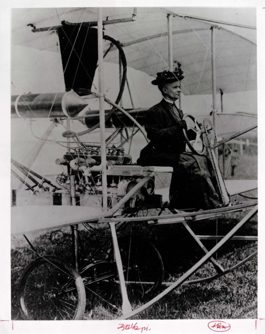 Woman seating at the steering wheel of an early airplane, wearing a hat
