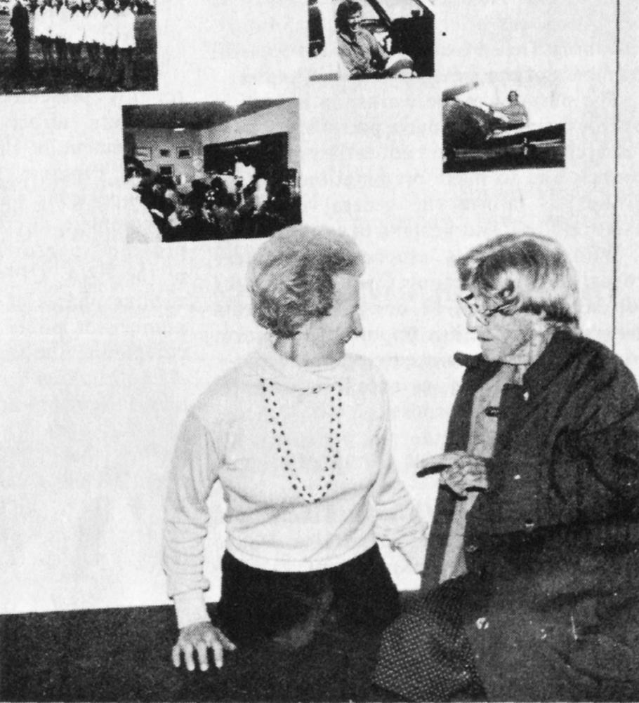 Black and white photograph of two women in front of a gallery wall with four photographs. Woman on the left wears a white shirt and a necklace. Woman on the right wears a dark jacket.