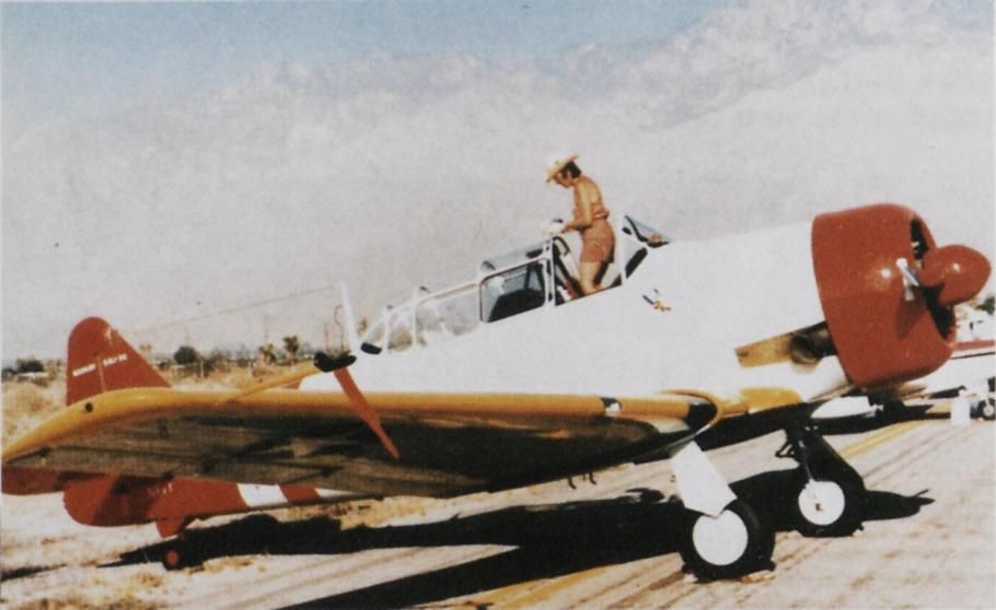 Right side view of woman in hat and khaki shorts stands in the cockpit of a white aircraft with yellow wings and red nose and tail. Front wheels are down.