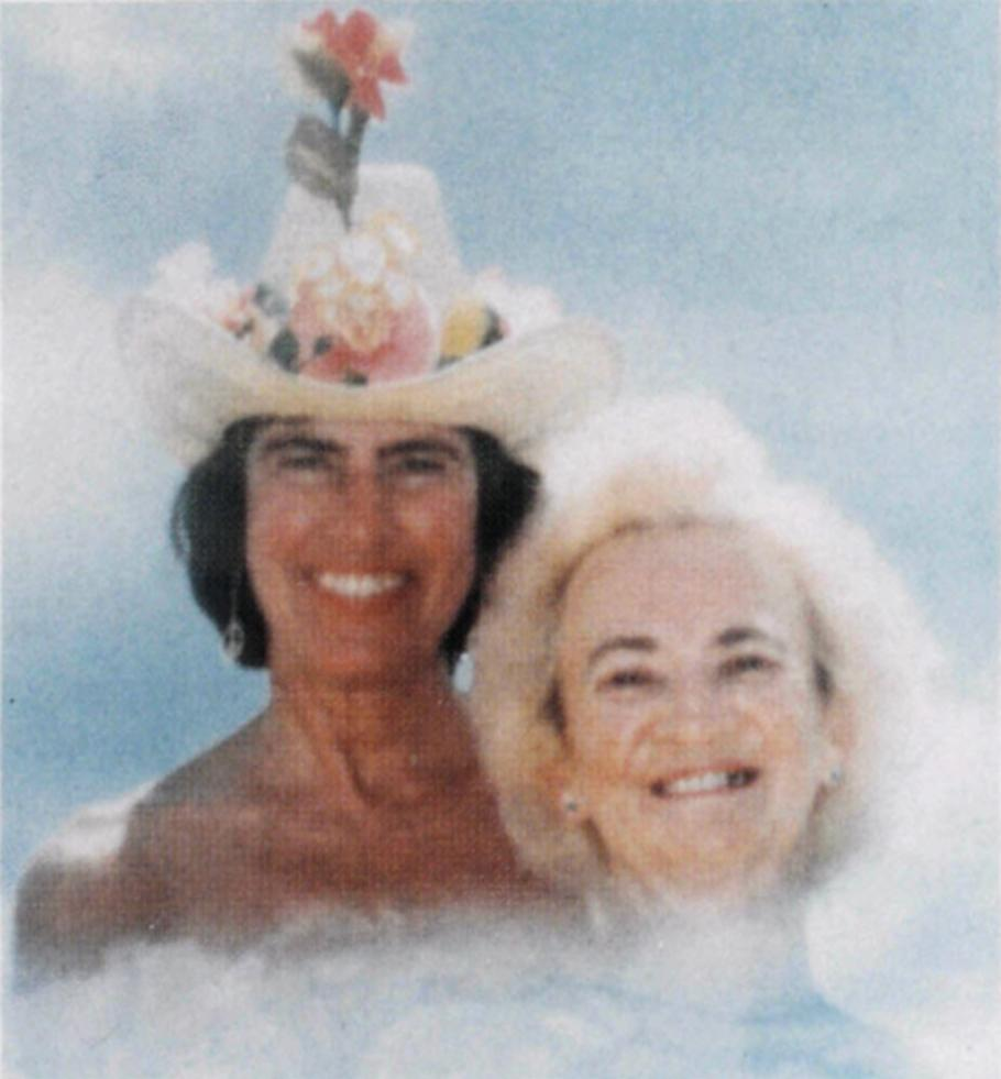 Two women in stylized clouds: Woman on the right has dark hair and is wearing a white cowboy hat with flowers sitting on the brim and pink hibiscus sticking out. Woman on right has white hair.
