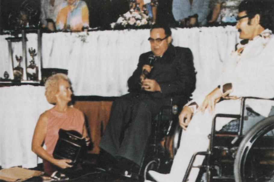 From right to left: woman in pink shirt holds a plaque (she is missing both legs and walking on her knees). Man wearing glasses and a black suit holds a microfilm, sitting in a wheelchair. Man in white suit sitting in wheelchair. Backdrop is banquet table