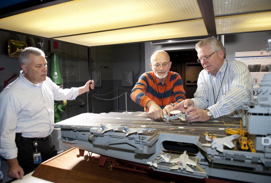 curator Chris Moore (left) looks on as Steve Henninger (center), assisted by Paul Moore, frees the E-2C on the model of the USS Enterprise.