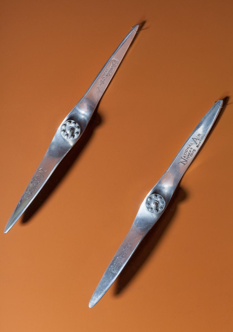 Two metal miniature propellers against an orange-red backdrop.
