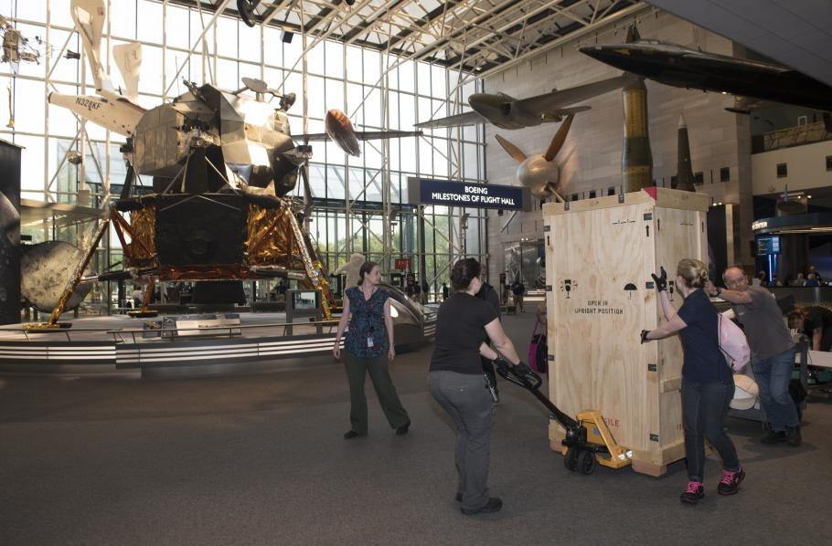 "Gene Cernan's Apollo 17 spacesuit being moved out of the exhibit case in the ""Apollo to Moon"" gallery"