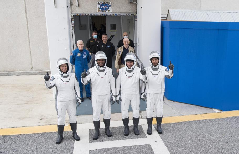 The crew of SpaceX Crew-1 stands in white spacesuits outside of the Neil A. Armstrong Operations and Checkout Building