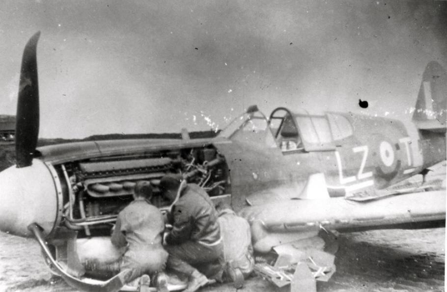 A photo of mechanics repairing damage to the belly of Kittyhawk IA 875, 1942.