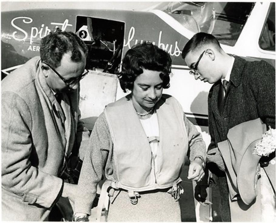 Black and White photograph: Airplane in the back has writing: Spirit of Columbus. Woman in the center has dark hair and wears and inflatable vest. Men on left and right wear glasses and are turning towards the woman.