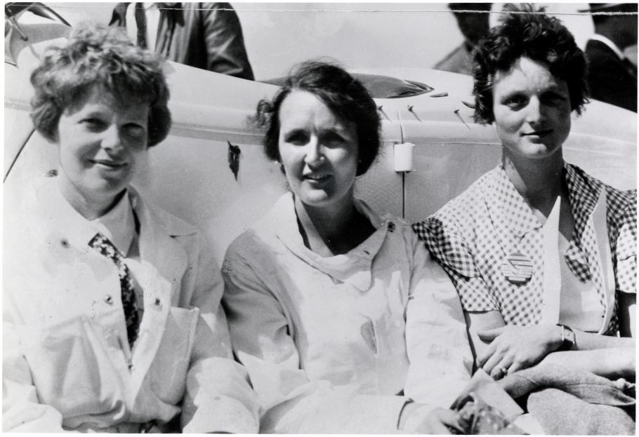 Earhart, Nichols, and Thaden sit shoulder to shoulder in this black and white photo.